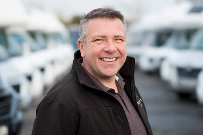 Headshot of company director in from of motorhomes